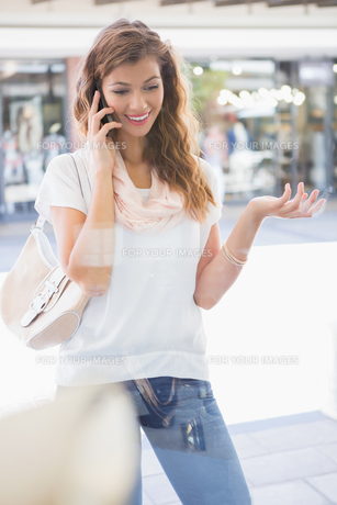 Smiling woman calling with smartphoneの素材 [FYI00009137]