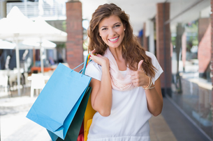 Portrait of smiling woman with shopping bags looking at camera and showing thumbs upの素材 [FYI00009138]