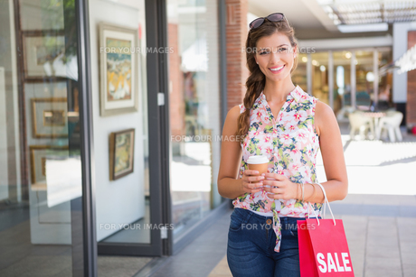 Portrait of smiling woman with sunglasses, coffee to go and shopping bagの写真素材 [FYI00009140]