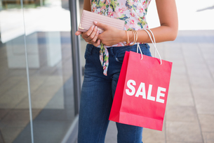 Woman holding wallet and shopping bagの写真素材 [FYI00009141]
