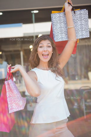 Portrait of euphoric woman raising shopping bagsの素材 [FYI00009142]
