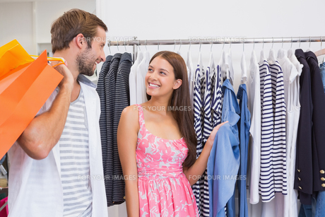 Smiling couple looking at clothesの写真素材 [FYI00009143]
