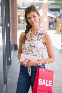 Portrait of smiling woman with sunglasses holding wallet and shopping bagの写真素材 [FYI00009144]