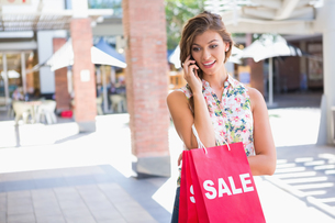 Smiling woman with sale shopping bags calling with smartphoneの素材 [FYI00009151]