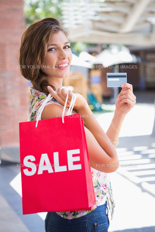 Portrait of smiling woman with sale shopping bag showing credit cardの写真素材 [FYI00009153]