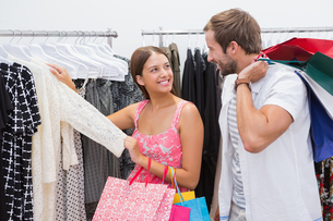 Smiling couple with shopping bags looking at clothesの写真素材 [FYI00009158]
