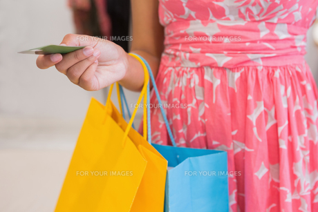 Woman with shopping bags paying by credit cardの素材 [FYI00009159]