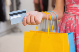 Woman with shopping bags paying by credit cardの写真素材 [FYI00009161]