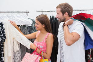 Smiling couple with shopping bags looking at clothesの写真素材 [FYI00009165]