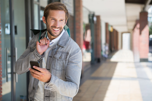 Young happy smiling man holding shopping bags and his mobileの素材 [FYI00009167]