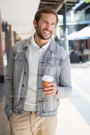 Young happy smiling man holding a a cup of coffeeの写真素材 [FYI00009170]