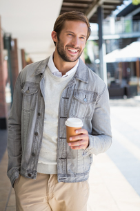 Young happy smiling man holding a a cup of coffeeの素材 [FYI00009170]