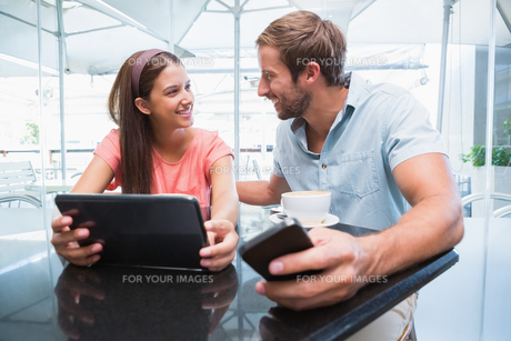 Young happy couple looking at each other with a laptop and a mobileの写真素材 [FYI00009178]