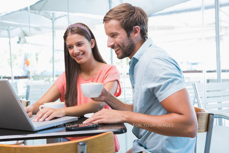 Young happy couple looking at a laptopの写真素材 [FYI00009179]