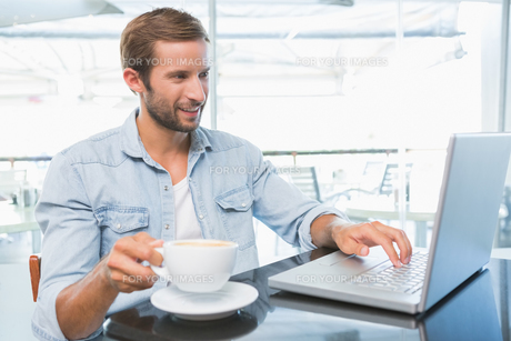 Young happy man typing on the laptop while holding his coffeeの写真素材 [FYI00009187]
