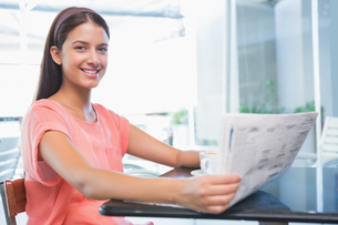 Young happy woman smiling at the camera while holding the newspaperの写真素材 [FYI00009193]