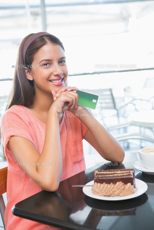 Young happy woman holding credit card and a cake in front of herの写真素材 [FYI00009195]