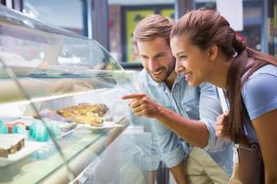 Young happy couple choosing cakeの写真素材 [FYI00009198]