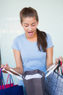 Young surprised woman looking at her shopping bagsの写真素材 [FYI00009199]