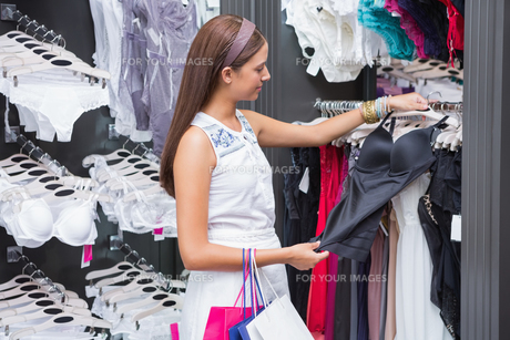 Young happy smiling woman looking at clothesの素材 [FYI00009200]