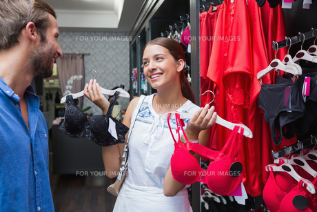 Young happy woman showing clothes to her husbandの素材 [FYI00009202]