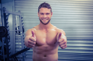 Portrait of smiling muscular man looking at camera with thumb upの素材 [FYI00009213]