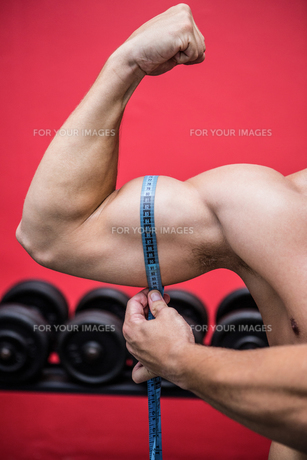 Muscular man measuring his musclesの写真素材 [FYI00009236]
