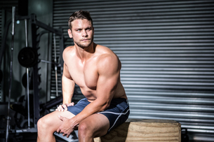 Focused muscular man sitting on a boxの写真素材 [FYI00009247]