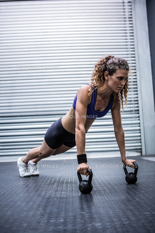 Muscular woman doing push-ups with kettlebellsの写真素材 [FYI00009261]