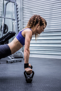 Muscular woman doing push-ups with kettlebellsの素材 [FYI00009267]