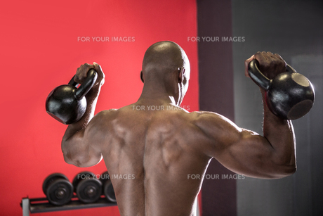 Back view of muscular man lifting two kettlebellsの素材 [FYI00009274]