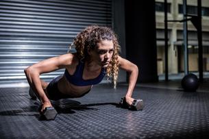 Muscular woman doing push-ups with kettlebellsの素材 [FYI00009277]