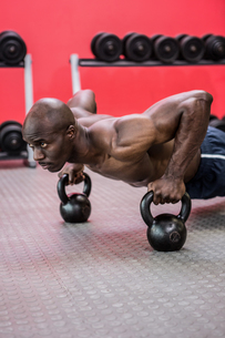 Muscular man doing push-ups with kettlebellsの素材 [FYI00009281]