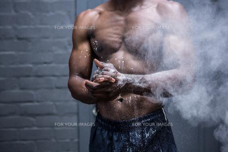 Young Bodybuilder shaking Chalk off his handsの写真素材 [FYI00009285]