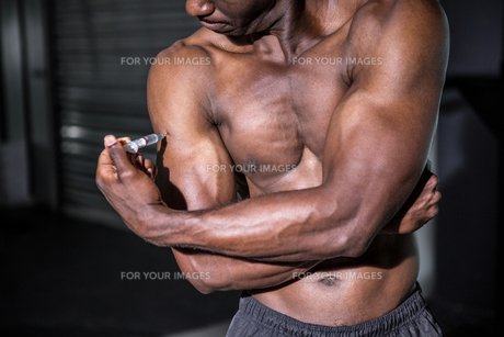 Young Bodybuilder injecting something into his armの写真素材 [FYI00009307]