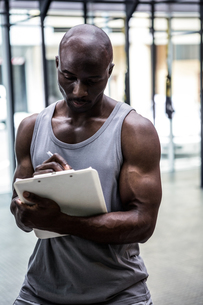 Young bodybuilder writing on a clipboardの写真素材 [FYI00009353]