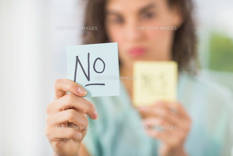 Smiling businesswoman holding yes and no sticksの素材 [FYI00009360]
