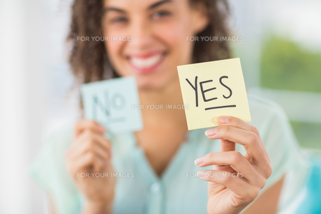 Smiling businesswoman holding yes and no sticksの素材 [FYI00009361]