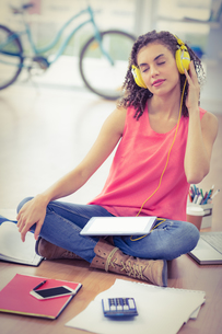 Young creative businesswoman listening to musicの写真素材 [FYI00009397]