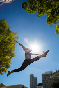 Athletic woman jumping in the air and doing splitの写真素材 [FYI00009598]