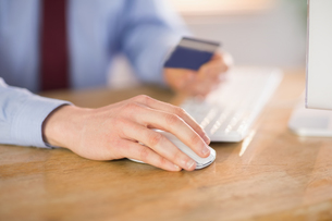 Businessman shopping online at deskの写真素材 [FYI00009606]