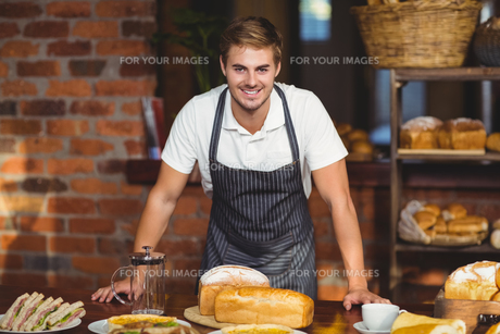 Handsome waiter bended over a food tableの写真素材 [FYI00009644]