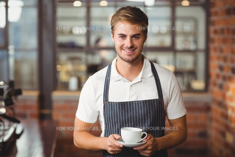 Handsome barista holding a cup of coffeeの写真素材 [FYI00009646]
