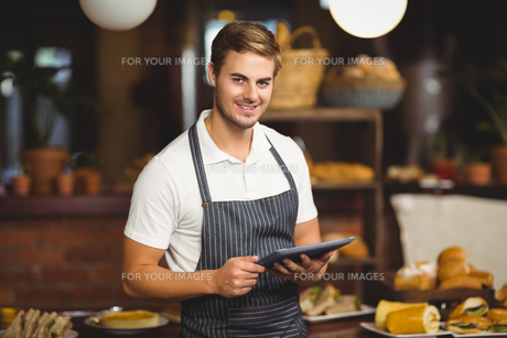 Handsome waiter holding a tabletの写真素材 [FYI00009647]
