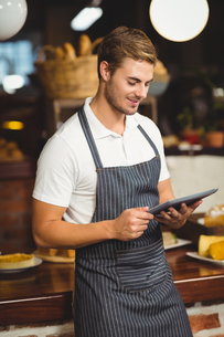 Handsome waiter using a tabletの写真素材 [FYI00009653]