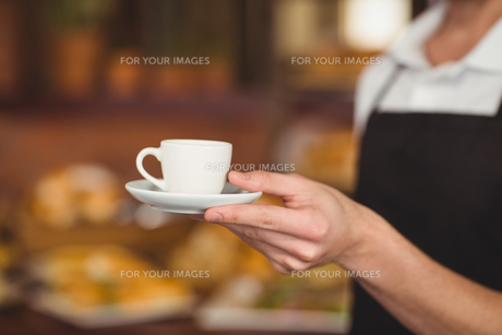 Barista offering cup of coffeeの写真素材 [FYI00009658]