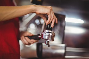 Close up view of a barista pressing coffeeの写真素材 [FYI00009661]