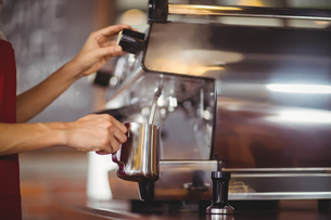 Barista steaming milk at the coffee machineの写真素材 [FYI00009663]