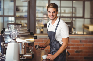 Handsome barista making a cup of coffeeの写真素材 [FYI00009665]