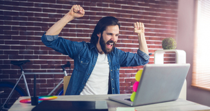 Cheerful creative businessman with arms raised looking at laptopの写真素材 [FYI00009666]